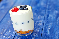 酸奶在桌上的玻璃用莓果和musli 免版税库存照片