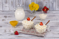 酸奶干酪、酸性稀奶油、牛奶、红色草莓和蜂蜜在桌上 库存照片