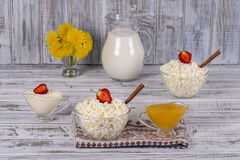 酸奶干酪、酸性稀奶油、牛奶、红色草莓和蜂蜜在桌上 免版税库存图片