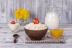 酸奶干酪、酸性稀奶油、牛奶、红色草莓和蜂蜜在桌上 库存图片