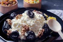 酸奶干酪和修剪在一个黑色的盘子 脯,在一个木箱的葡萄干 附近有一把木匙子 图库摄影