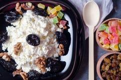 酸奶干酪和修剪在一个黑色的盘子 脯,在一个木箱的葡萄干 附近有一把木匙子 免版税库存照片