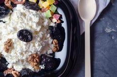 酸奶干酪和修剪在一个黑色的盘子 附近有一把木匙子 免版税库存图片