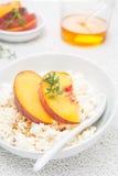 酸奶干酪用蜂蜜,胡说和新鲜的桃子,特写镜头 库存照片
