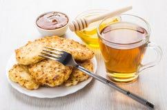 酸奶干酪薄煎饼、蜂蜜、杏子果酱和茶在桌上 图库摄影