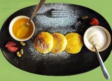 酸奶干酪薄煎饼或俄国sirniki用蜂蜜和酸c 库存照片