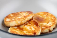 酸奶干酪薄煎饼或syrniki用莓果果酱在灰色板材,特写镜头视图 免版税库存照片