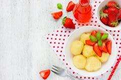 酸奶干酪饺子用在白色backgr的新鲜的草莓 免版税库存图片