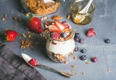 酸奶燕麦格兰诺拉麦片用新鲜的莓果、坚果、蜂蜜和薄荷叶在玻璃瓶子在灰色具体织地不很细背景 免版税图库摄影