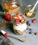酸奶燕麦格兰诺拉麦片用新鲜的莓果、坚果、蜂蜜和薄荷叶在玻璃瓶子在灰色具体织地不很细背景 库存照片