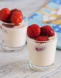 酸奶用在一块玻璃的草莓在与蓝色餐巾的木桌上 库存照片