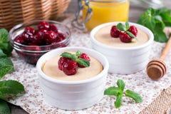 酸奶用在一张木桌上的新鲜的水多的樱桃 免版税图库摄影