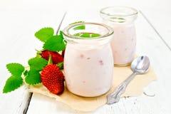 酸奶用在瓶子的草莓在羊皮纸和委员会 免版税库存图片