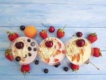 酸奶,在蓝色木背景的燕麦粥蓝莓草莓牛奶店可口茶点杏子樱桃 免版税图库摄影