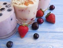 酸奶,燕麦粥蓝莓草莓茶点在蓝色木背景的杏子樱桃 库存照片