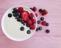 酸奶,草莓,莓,自创自然节食的茶点的蓝莓桃红色木背景, 库存照片