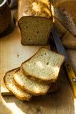 酸面团大面包切开了成在木切板,刀子,厨房用桌,阳光斑点的切片,舒适 库存图片