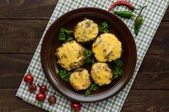 酿蘑菇用在黏土的蒜味咸腊肠和无盐干酪乳酪在木背景滚保龄球 图库摄影