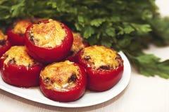 酿蘑菇蕃茄用乳酪在绿色荷兰芹背景的烤箱烘烤了  豆黄瓜断送素食新鲜的油煎的骨髓的蕃茄 免版税图库摄影