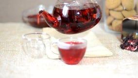酿造处理红色茶服务桌早餐,在茶壶的红色茶 茶叶、木槿和两个玻璃杯子与 股票录像