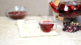 酿造处理红色茶服务桌早餐,在茶壶的红色茶 茶叶、木槿和两个玻璃杯子与 股票视频