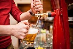 酿造草稿,在客栈的未过滤的啤酒的男服务员 免版税库存照片