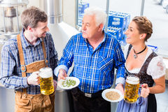 酿酒者和夫妇在被引导的啤酒啤酒厂游览 免版税库存图片