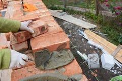 酿酒者 安装红色块和填隙砖石工的瓦工工作者联接有修平刀轻轻一击的外部砖房子墙壁 免版税图库摄影