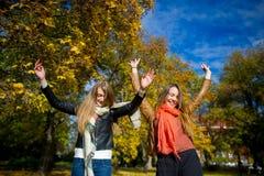醇厚的秋天 两个女孩是学生快乐地花费时间在城市公园 免版税库存图片