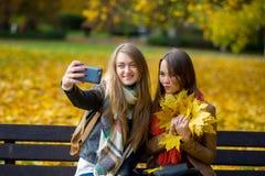 醇厚的秋天 两名逗人喜爱的学生在公园做一selfie 免版税图库摄影