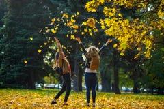 醇厚的秋天 学生的两个快乐的女孩在公园走 免版税库存图片