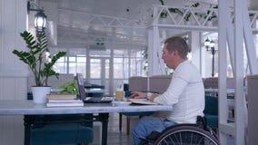 醉心工作,轮椅的自由职业者无效人谈话在一个手机和与坐在桌上的膝上型计算机一起使用 股票录像