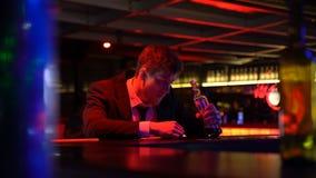 醉酒的从瓶的人饮用的威士忌酒偏僻在客栈,落在酒吧柜台 股票录像