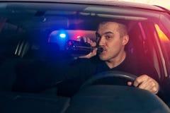 醉酒的司机由警察追逐了,当驾驶汽车时 图库摄影