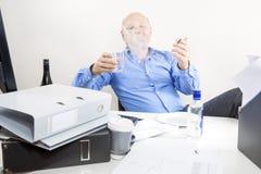 醉酒的商人在办公室抽烟和饮料 免版税库存照片