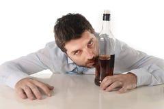 醉酒的商人被浪费和在酒精中毒的威士忌酒瓶 库存图片