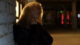 醉酒的夫人站立的单独外部夜总会和遭受可怕的头疼 股票视频