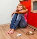醉酒的妇女坐地板在厨房 免版税库存照片