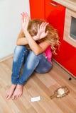 醉酒的妇女坐地板在厨房 图库摄影