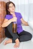 醉酒的拉丁妇女坐拿着瓶的洗手间地板 免版税图库摄影