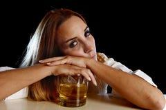醉酒的醺酒的妇女浪费了倾斜沮丧在苏格兰威士忌酒玻璃 免版税库存图片