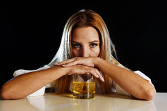 醉酒的醺酒的妇女浪费了倾斜沮丧在苏格兰威士忌酒玻璃 库存照片