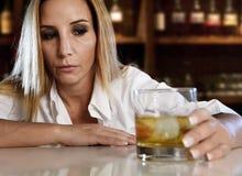 醉酒的醺酒的妇女浪费了喝在酒吧的苏格兰威士忌酒 免版税库存照片