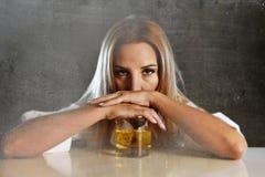 醉酒的醺酒的妇女被浪费和沮丧拿着苏格兰威士忌酒玻璃被喝 免版税库存图片