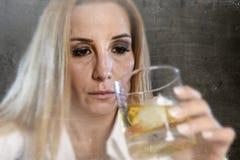 醉酒的醺酒的妇女被浪费和沮丧拿着苏格兰威士忌酒玻璃被喝 免版税图库摄影