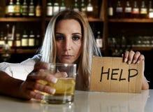 醉酒的醺酒的白肤金发的妇女饮用的酒精请求帮忙在酒吧或客栈 库存图片