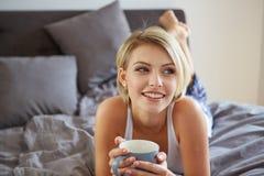 醒与的愉快的微笑的美丽的白肤金发的妇女 免版税库存照片