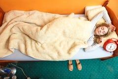 醒与闹钟的不快乐的妇女 免版税库存照片