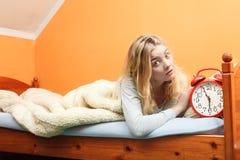 醒与闹钟的不快乐的妇女 库存图片