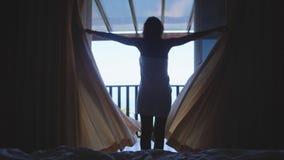 醒从床的美丽的女孩佩带白色毛巾打开帷幕并且去海视图大阳台 15个妇女年轻人 库存图片